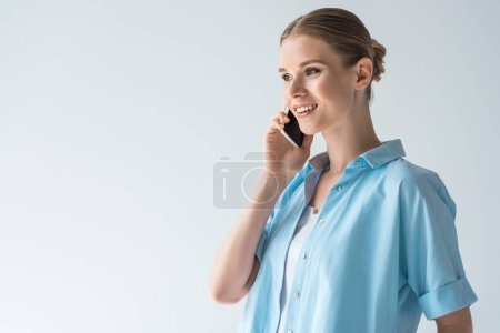 happy young woman in blue shirt talking by phone isolated on white