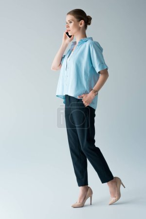 beautiful young woman in blue shirt talking by phone on grey