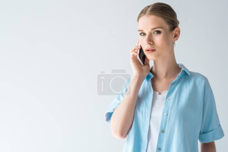 beautiful young woman in blue shirt talking by phone isolated on white
