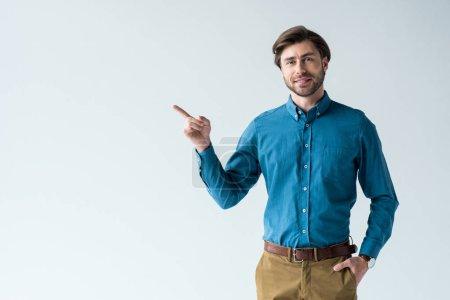 Photo pour Beau jeune homme dans la collection de vêtements casual pointant sur espace isolé sur blanc - image libre de droit