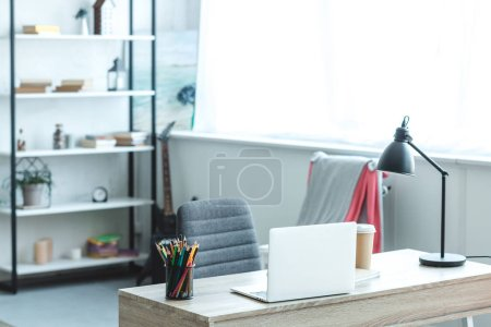 laptop and coffee to go on wooden desk in cozy room with modern interior