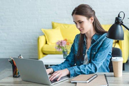 Photo pour Sourire fille à l'aide d'un ordinateur portable tout en étudiant à la maison - image libre de droit