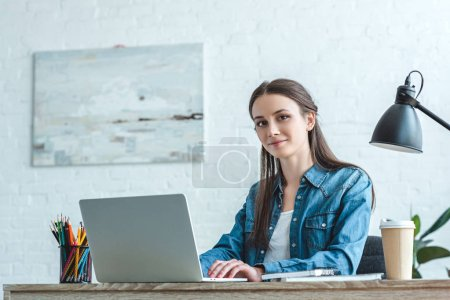 attractive girl smiling at camera while using laptop at desk