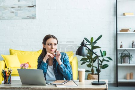 pensive girl talking by smartphone and looking away while studying with laptop and notebooks at home