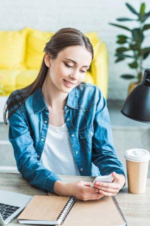 hermosa niña sonriente con smartphone sentado en el escritorio y estudiando en casa