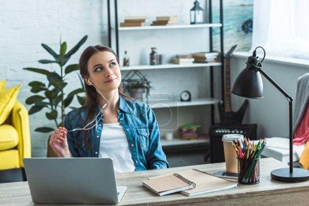 Photo pour Adolescent coûteux dans les écouteurs assis à la table et regardant loin tout en étudiant avec ordinateur portable à la maison - image libre de droit