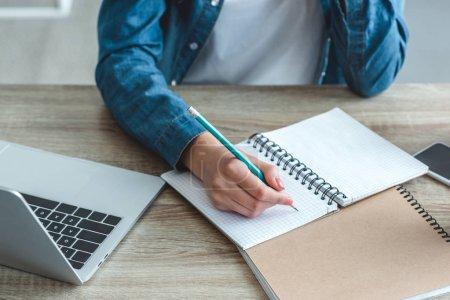 Photo pour Gros plan vue partielle de fille écrivant dans un cahier tout en étudiant avec ordinateur portable au bureau - image libre de droit