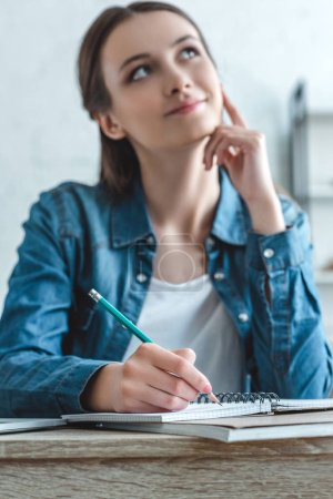 selective focus of pensive smiling girl writing in notebook and looking away while studying at home