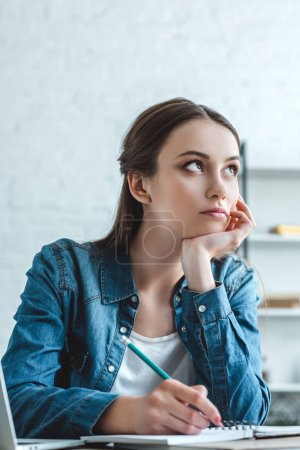 pensive girl with hand on chin taking notes and looking away while studying at home