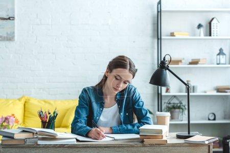 Photo pour Concentré d'adolescente d'écriture et d'étudier au bureau à la maison - image libre de droit