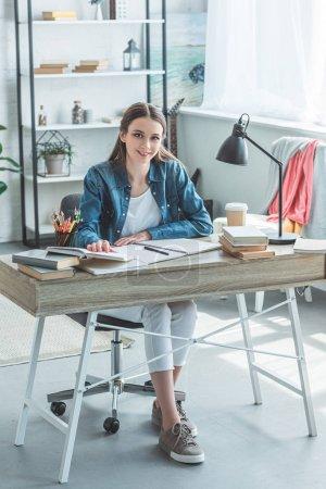 beautiful teenage girl smiling at camera while sitting at desk and studying at home