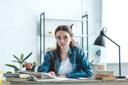 Photo for Attractive teenage girl sitting at desk and looking at camera while studying at home - Royalty Free Image