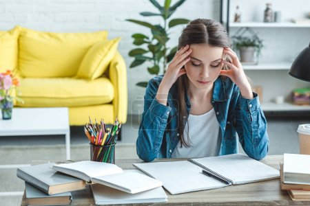Photo for Concentrated girl with headache sitting at desk and studying at home - Royalty Free Image