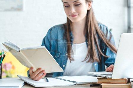 Photo pour Souriant fille tenant livre et en utilisant un ordinateur portable tout en étudiant à la maison - image libre de droit