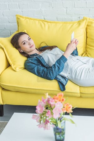 beautiful girl in earphones looking at camera while lying on sofa and using smartphone
