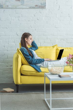 side view of young woman using laptop with blank screen on sofa at home