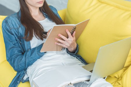 cropped shot of girl writing in notebook and using laptop on sofa at home
