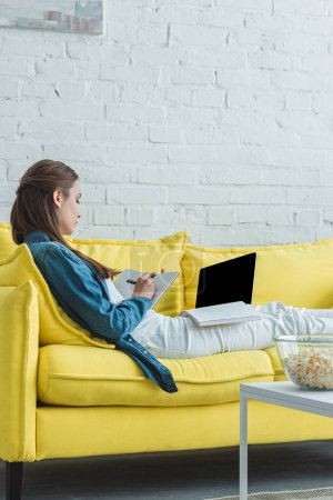 girl taking notes in notebook and using laptop with blank screen on sofa at home