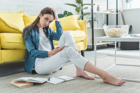 bored teenage girl holding smartphone and looking at camera while sitting on carpet and studying at home