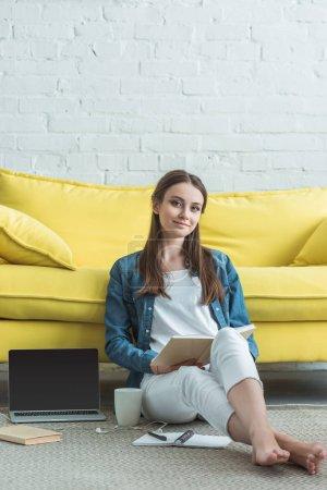 Photo pour Belle adolescent fille lecture livre et sourire à la caméra tout en étant assis sur le tapis et étudier à la maison - image libre de droit