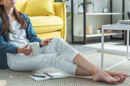 Photo for Cropped shot of barefoot girl holding cup while sitting on carpet and studying at home - Royalty Free Image