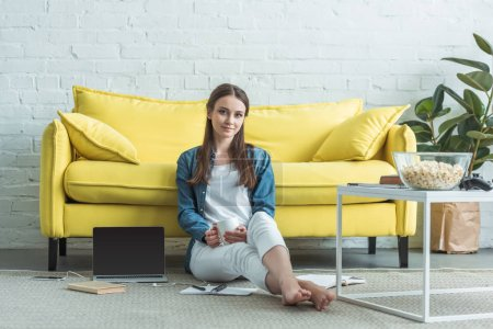 beautiful girl sitting on carpet and smiling at camera while holding cup and studying at home