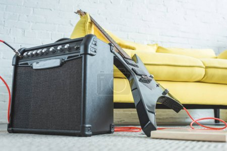 Photo for Electric guitar and loud speaker standing on floor near sofa - Royalty Free Image