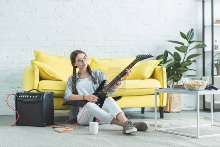 female teen musician playing electric guitar on floor in living room