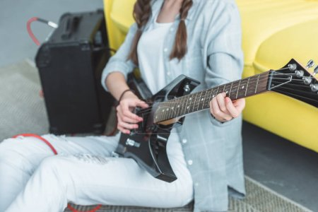 cropped view of girl playing electric guitar at home