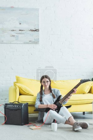 attractive teen girl playing electric guitar in living room