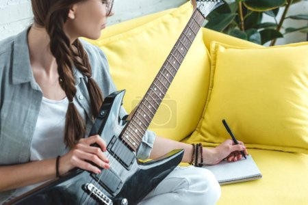 attractive teen girl playing electric guitar and writing song
