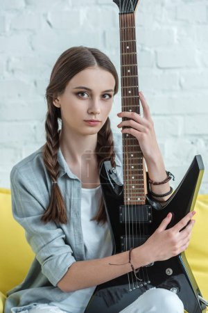 attractive teen musician with electric guitar sitting on sofa