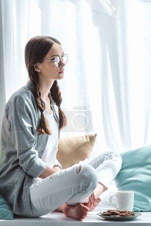beautiful teen girl sitting on windowsill with cup of tea and cookies