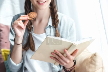 cropped view of girl reading book and eating cookie