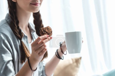 cropped view of girl eating cookies with coffee
