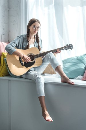 beautiful teen girl playing acoustic guitar while sitting on windowsill with pillows