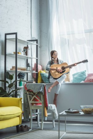 teen girl playing acoustic guitar while sitting on windowsill in living room