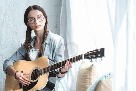 Photo pour Belle adolescente, jouer de la guitare acoustique près de fenêtre - image libre de droit