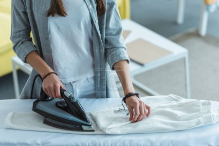 cropped view of girl ironing white pants at home