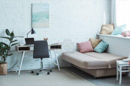 Foto de Sofá con cojines y mesa de ordenador portátil en la sala de estar - Imagen libre de derechos