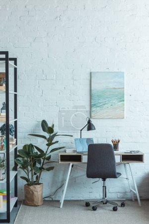 Bücherregal und Tisch mit Laptop im Wohnzimmer mit Wandmalerei