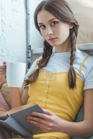 beautiful teen girl with cup of coffee and book