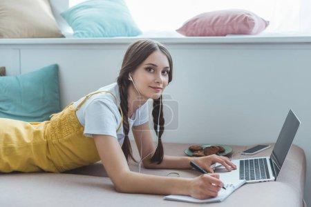 teen girl lying on sofa with laptop, textbook, smartphone, earphones and cookies