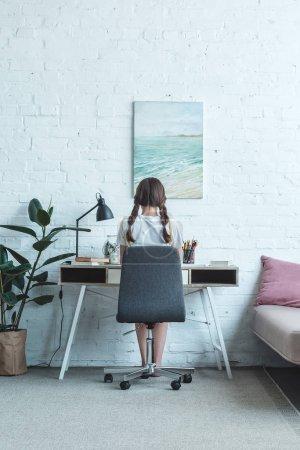 Photo pour Vue arrière de la fille assise à la table dans la chambre avec peinture sur le mur - image libre de droit