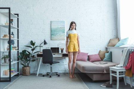 Photo pour Belle teen fille debout dans la salle de séjour avec sofa, étagère et portable sur la table - image libre de droit