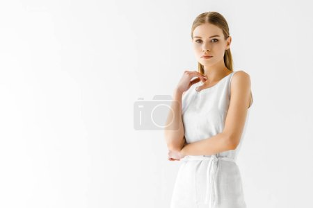 attractive woman in linen white dress posing with hand on neck isolated on grey background