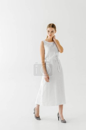 beautiful woman in linen white dress posing with hand on neck isolated on grey background