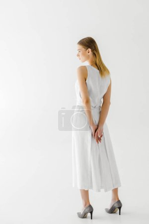 Photo for Rear view of attractive woman in linen white dress posing isolated on grey background - Royalty Free Image