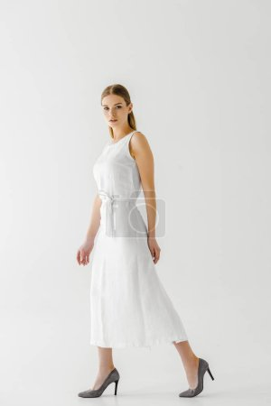 young woman in linen white dress posing isolated on grey background