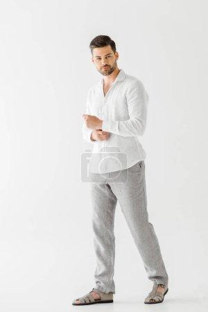 bel homme en vêtements en lin posant isolé sur fond gris